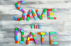 Phrase SAVE THE DATE composed with colorful blocks on wooden background stock image