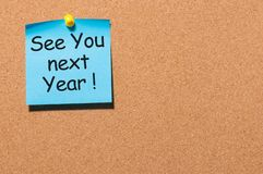 Phrase See you next year pinned at cork board with empty space for text, template royalty free stock images