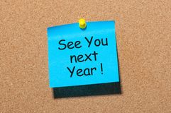 Phrase See you next year pinned at cork board royalty free stock photo