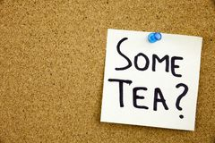 A yellow sticky note writing, caption, inscription Phrase SOME TEA in black ext on a sticky note pinned to a cork notice board. Phrase SOME TEA in black ext on a Stock Images