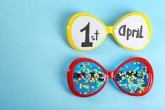 Phrase. `1st April`, glasses and confetti on color background. Fool`s day celebration Stock Photography