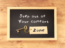The phrase step out of your comfort zone written on blackboard.  stock photos