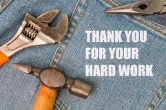 Phrase THANK YOU FOR YOUR HARD WORK written on blue jeans with hammer, wrench and pliers