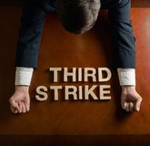 Phrase Third Strike and devastated man composition stock image