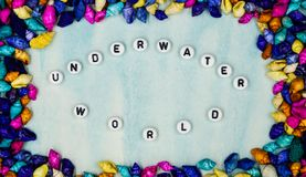 The phrase `Underwater world`, has been posted within the framework of small colorful shells on a blue background. Stock Photos