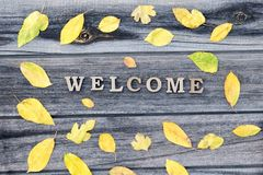 Phrase Welcome on a wooden background, frame of yellow leaves Stock Photography