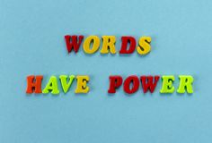 Phrase `words have power` of colored plastic magnetic letters on blue paper background.  stock photography