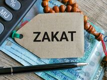 Free Phrase ZAKAT Written On Label Tag With Money,prayer Beads And Calculator. Stock Photo - 213657250