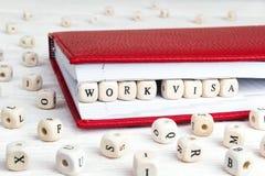 Phrasen-Arbeitsvisum geschrieben in Holzklötze im roten Notizbuch auf weißen Holztisch stockfoto