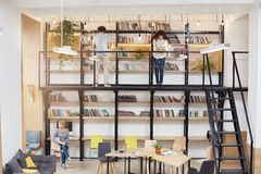 Phto of big modern univesity library. Blonde girl sitting on chear looking in window with dreamy face expression. Two. Young people standing near bookshelves Stock Photo