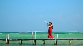 Phu Quoc Island. The woman in a red dress walks on a pier with a green backpack. The traveler photographs herself on. On this video you can see as the woman in a stock footage
