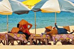 Beach masseuses resting under umbrellas Stock Photography