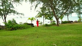 Phu Quoc. Walk in a tropical garden. Beautiful Woman in Red Dress Walking in Tropical Garden. The tropical island in the. On this video you can see as the woman stock video