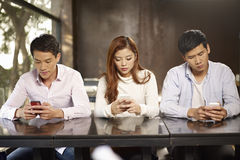 Phubbing. Young people playing with smartphones and ignoring each other royalty free stock photo