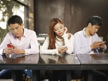 Phubbing. Young people playing with smartphones and ignoring each other