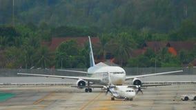 Phuket airport traffic. PHUKET, THAILAND - DECEMBER 2, 2016: Bangkok airways ATR 72 towing and IKAR Boeing 767 in Pegas livery taxiing after landing. Rainy stock video