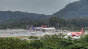 Phuket airport traffic at rain. Airbus 330 Thai airways, Boeing 767 Asia Atlantic Airlines at apron, and Airbus 320 AirAsia turn to wet runway of Phuket airport stock video footage
