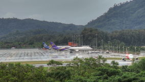 Phuket airport traffic at rain. Airbus 330 Thai airways, Boeing 767 Asia Atlantic Airlines at apron, and Airbus 320 AirAsia turn to wet runway of Phuket airport stock video