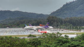Phuket airport traffic at rain. Airbus 330 Thai airways, Boeing 767 Asia Atlantic Airlines at apron, and Airbus 320 AirAsia turn to wet runway of Phuket airport stock footage