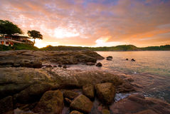 Phuket beach at Sunrise with interesting rocks in foreground Royalty Free Stock Image