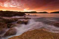 Phuket beach at Sunrise with interesting rocks in foreground Stock Photography