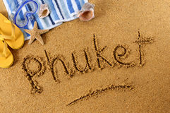 Phuket Thailand beach sand word writing. The word Phuket written on a sandy beach, with scuba mask, beach towel, starfish and flip flops Royalty Free Stock Image
