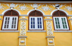 Phuket City, Thailand: Restored Chinese Shop House. Detail of three windows and white bas relief pargetting designs adorning a fine late 19th century former Stock Photos