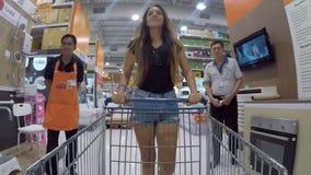 Phuket - 27 de dezembro: Mulher asiática nova que empurra o carrinho de compras na loja com bens da casa Timelapse de HD Gopro ta filme