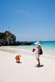 PHUKET - 16 DE MARZO: Muchacha feliz del pequeño niño que juega en la playa MARCHA Foto de archivo libre de regalías