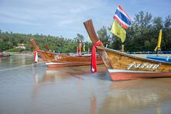 Thai wooden boats stand in the morning on the beach. PHUKET ISLAND, THAILAND - JANUARY: Phuket Island - the most expensive resort in Thailand Royalty Free Stock Photos