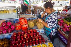 Phuket, Tailândia, em março de 2013, pealing tailandês da mulher do fruto do durian no mercado livre fotos de stock royalty free