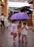 PHUKET, TAILÂNDIA - 17 DE AGOSTO DE 2018: Crianças que andam na chuva sob um guarda-chuva no shopping de Jungceylon na cidade de  Fotos de Stock