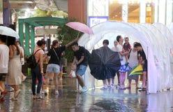 PHUKET, TAILÂNDIA - 17 DE AGOSTO DE 2018: Os visitantes do shopping de Jungceylon tentam esconder da chuva de queda Fotografia de Stock Royalty Free