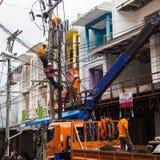 PHUKET, TAILANDIA - 22 DE MARZO DE 2017: Fijación de la línea eléctrica Electricistas que trabajan con los alambres de alto volta fotos de archivo libres de regalías
