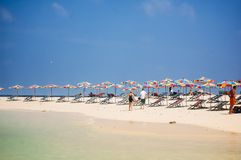 Phuket, Tailandia - 2009: Le sedie di spiaggia e gli ombrelli colourful allineano la spiaggia fotografia stock libera da diritti