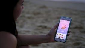 Phuket, Thaïlande - 28 mars 2017 : la femme jouant le pokemon vont sur son iphone 6s plus le pokemon disparaissent jeu multijoueu Photo libre de droits