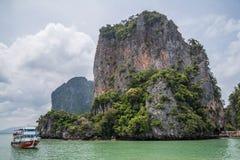 Phuket, Thailand - circa September 2015: Boat sails near limestone cliffs of Andaman Sea, Phang Nga Bay,  Thailand Royalty Free Stock Photos