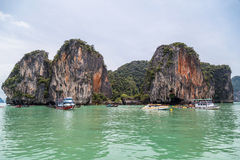 Phuket, Thailand - circa September 2015: Boats sails near limestone cliffs of Andaman Sea, Phang Nga Bay,  Thailand Royalty Free Stock Photos