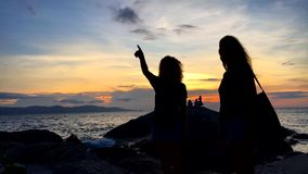 Phuket, Thailand- 20 DEC 2016: Two young happy girls watching flying airplane at beautiful sunset and having fun. stock video