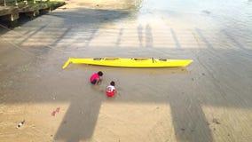 Phuket, Thailand- 01 FEB 2016: Two little thai girls play on sand at beach near canoe. Phuket, Thailand- 01 FEB 2016: Two little girls play on sand at beach near stock footage