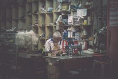 PHUKET, THAILAND-FEBRUARY 23, 2018 : Old shoemaker woking in his royalty free stock images