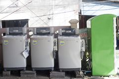 Public coin laundry on city street in Phuket, Thailand. Phuket, Thailand - 25 February 2018: Public coin laundry on city street. Row of washing machines for self royalty free stock photo