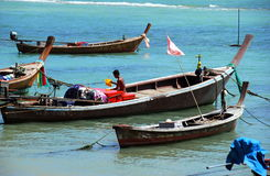 Phuket, Thailand: Fisherman in Longboat. A Thai fisherman sitting in his longboat prepares to set sail for a day's work on the Andaman Sea at Chao Lo Fishing Stock Image