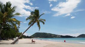 Phuket, Thailand - July 20, 2020 : Young woman swing on a beach few people at the Patong beach due to Covid-19