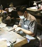 PHUKET THAILAND - JUNI 29, 2018: En juvelerare på arbete Ädelstengalleri på den Phuket ön, Thailand Arkivfoton