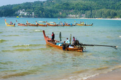 PHUKET, THAILAND - 19 MAR 2013: Man cast off on wooden long boat Stock Photos