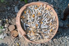Phuket, Thailand - March 27, 2019: Cigarette butts in ashtray with sand at smoking point. stock photos