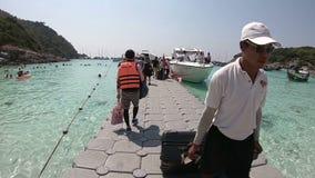 Phuket, Thailand - March 27, 2018 : Tourists walking on grey pontoon bridge to speedboat at Patok Bay, Koh Racha Yai Island.  stock video footage