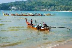 PHUKET THAILAND - 19 MARS 2013: Man som gjutas av på det trälånga fartyget Arkivfoton