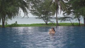 Mom with a two-year-old daughter in hotel pool near ocean. PHUKET, THAILAND - NOVEMBER 30, 2016: Young woman with a two-year-old daughter in hotel pool, teaches stock footage